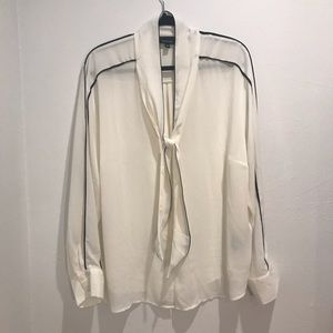 White blouse with black piping and attach scarf.